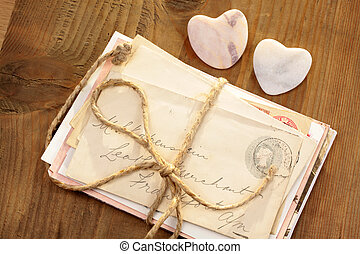 Stone hearts with old tied letters on wooden desk