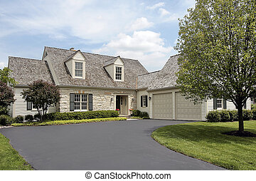 Suburban stone home with cedar shake roof