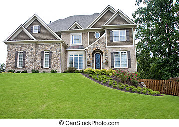A nice stone house atop a green manicured lawn against a white background