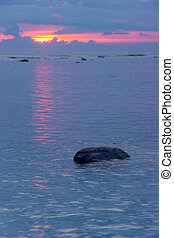 Stone in sea at sunset