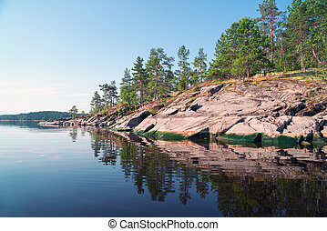Stone island with a reflection in the water on the lake . Ladoga Skerries, Karelia.