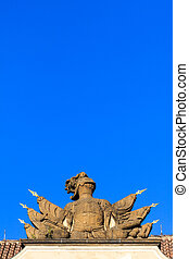 Stone knight armor statue on a roof under blue sky