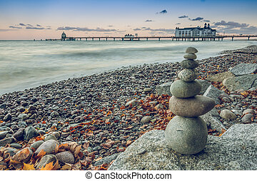 stone man on the baltic sea with jetty in background