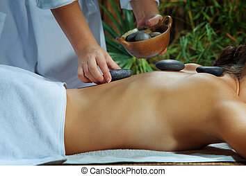 stone massage - portrait of young beautiful woman in spa ...