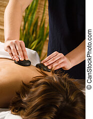 woman in a day spa getting a hot stone massage