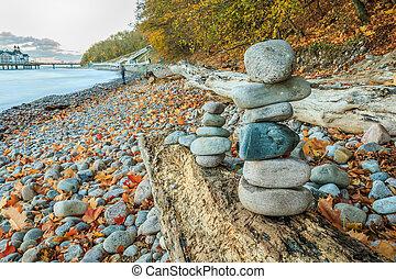 Stone men on a log on the Baltic Sea coast in autumn