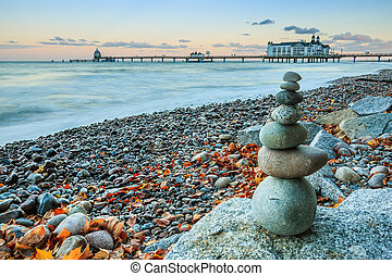Stone men on Baltic coast with pier in background