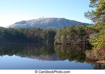 Stone Mountain with trees in freground reflected in a still lake.