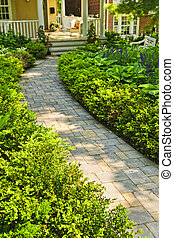 Stone path in landscaped home garden - Paved stone path in...