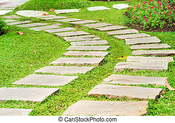 Stone path in park on green grass