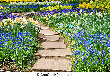 Stone path winding in spring flower garden