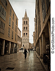 Stone paved dalmatian street in Zadar with church tower,...