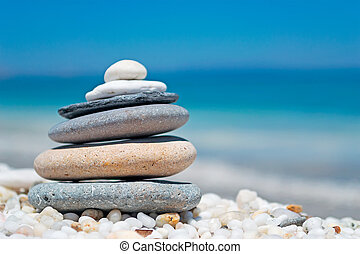 stone pile on white pebbles by the shore