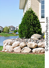 Stone Retaining Wall and Evergreen Shrub at a Residential...