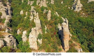 Stone rock needles stick out of the forest on the...