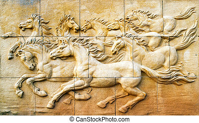 Stone sculpture of horse on wall