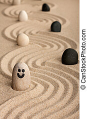 Stone smiley sticking out of the sand, between white and black stones