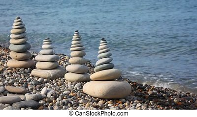 stone stack on pebble seacoast, waving sea in background