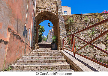 Stone staircase enters the arch with a lantern and a blue ...