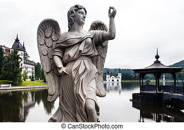 Stone statue of an angel on the lake