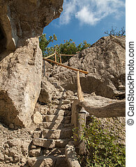 Stone steps with wooden handrails leading up to the top of a rocky mountain