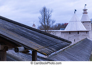 Stone tower or turret of ancient or antique kremlin or fortress with wood roof in the cloudy spring or autumn weather