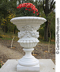 Stone vase in the old classical style with flowers in the park