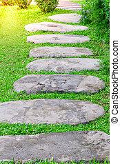Stone walk on the green grass