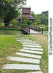 stone walk way and wood bridge in park