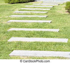 Stone walk way winding in a garden.