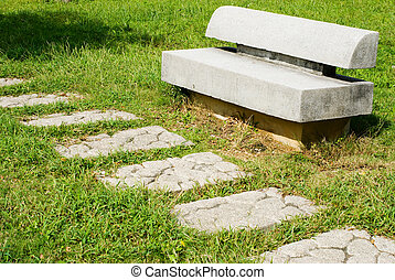 Stone walkway and stone bench on grass land