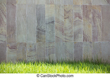 Stone wall and green grass background