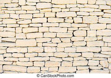 Stone wall background, pattern, texture, wallpaper. Exterior construction in Provence, Cote Azur, France, Europe.