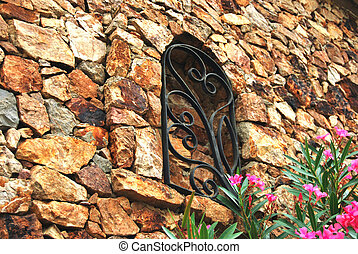 Decorative brown stone wall and oleander tree