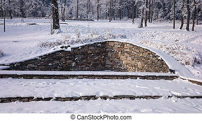 Stone wall in mountains covered with fresh snow