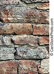 Stone wall macro closeup, stonewall pattern background, vertical old aged weathered red and grey grunge limestone dolomite calcium carbonate hard sedimentary slate slab rock texture, natural grungy textured bricks, beige, yellow, reddish, gray brick vintage
