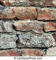 Stone wall macro closeup, stonewall pattern background, old aged weathered red and grey grunge limestone dolomite calcium carbonate hard sedimentary slate slab rock texture, natural grungy textured bricks, beige, yellow, reddish, gray brick vintage