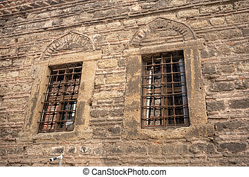 Stone wall of an old building, with a grate on the window