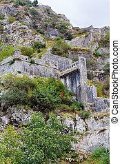 stone wall of the fortress on a steep mountain slope