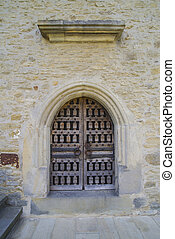 Stone wall with barred wooden door