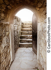 Stone wall with open door and rays of light behind