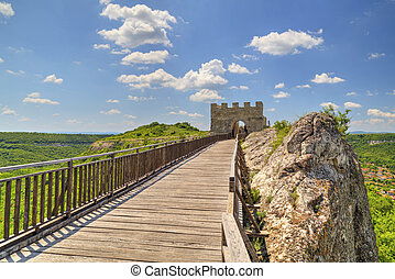 Stone walls and gate with wooden bridge