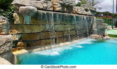 Stone waterfall, stream of water pouring into, pool - Stone...