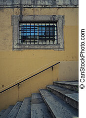 Stone window with metal bars, in a yellow wall with stairs underneath