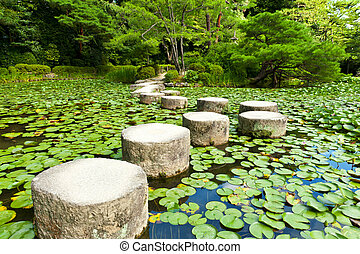 Zen stone path in a Japanese Garden near Heian Shrine. Stones are surrounded by lotus leaves