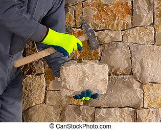 stonecutter mason with hammer and stone working masonry -...