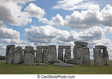 Stonehenge historic site on green grass under blue sky....