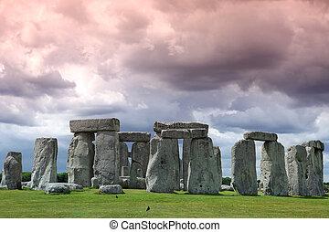 Stonehenge historic site on green grass under cloud sky. ...