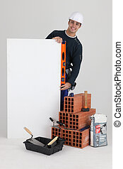 Stonemason posing with his tools, building materials and a blank sign
