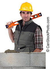 Stonemason standing before a wall and carrying a spirit level